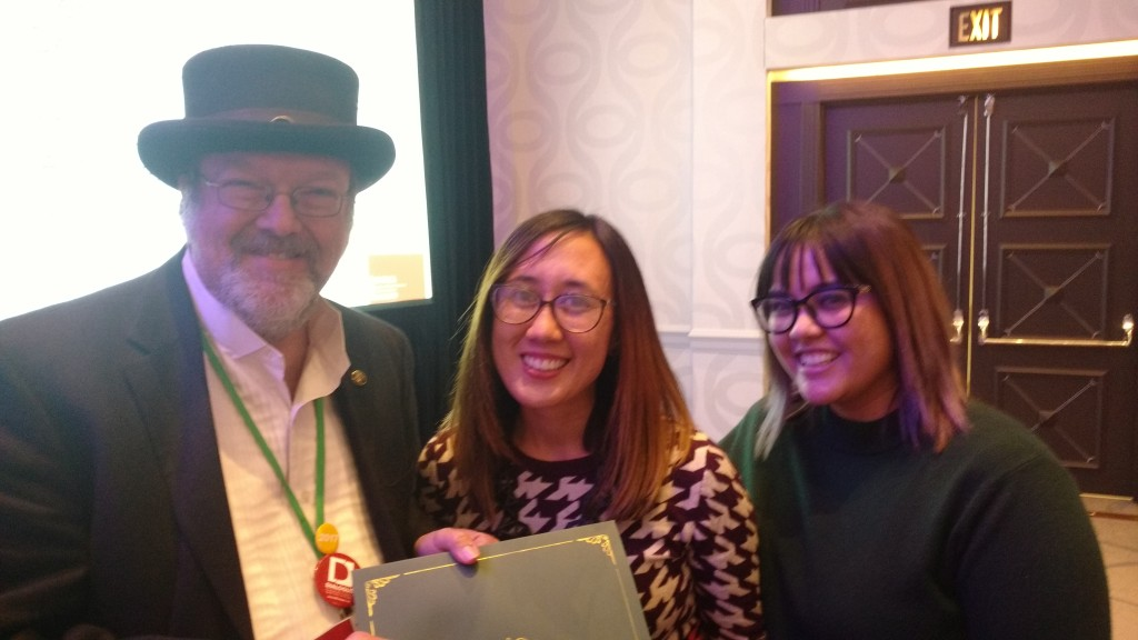 "Maggie Melo and Antonnet Johnson, graduate students at the University of Arizona, receive the Graduate Paper Award for Popular Culture Pedagogy from Kurt Depner, a judge for the award, for their project, ""Teaching Technical Writing through Designing and Running Escape Rooms."""