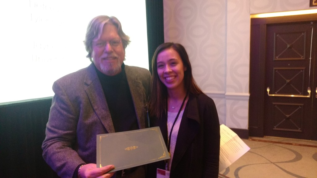 "Jayne Simpson, graduate student at the University of Texas San Antonio, receives the Graduate Paper Award for Television, Music, and Visual Media from Chuck Hamilton, a judge for the award, for her paper, ""Country Love Songs as Support of Detrimental Ideas of Masculinity: Tyler Farr's 'Redneck Crazy.'"""